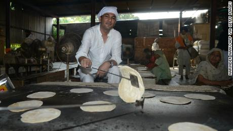 Vikas Khanna, MasterChef India host and executive chef of Junoon restaurant in New York, prepares a  chappati (flat bread) for a communal vegetarian meal at the Sikh Shrine Golden temple in Amritsar on September 7, 2016.