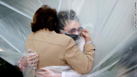 Olivia Grant hugs her grandmother Mary Grace Sileo through a plastic cloth in Wantagh, New York.