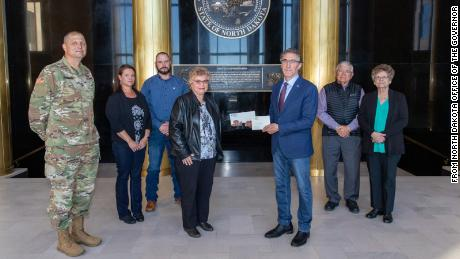 Gov. Doug Burgum presents Ronald Hepper's dog tag to his wife Ruth. They were joined by (from left) Maj. Gen. Al Dohrmann, Hepper's daughter Julie Hornbacher and her husband, Jim, and Ron Hepper's brother Stanley Hepper and his wife, Kathleen.