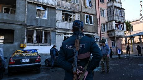 A police officer stands in front of a damaged apartment building in Stepanakert, during the ongoing conflict.