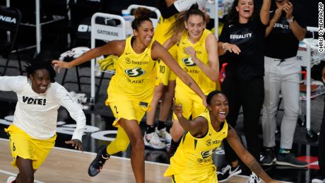 Members of the Seattle Storm rush the court after the team defeated the Las Vegas Aces to win the WNBA Championship in Bradenton, Florida, on Tuesday, October 6, 2020.