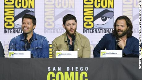 """Misha Collins, Jensen Ackles, and Jared Padalecki speak at the """"Supernatural"""" panel during 2019 Comic-Con International at San Diego Convention Center on July 21, 2019 in San Diego, California. The show became a major draw during the annual event, taking over the largest venue, Hall H, for several years."""