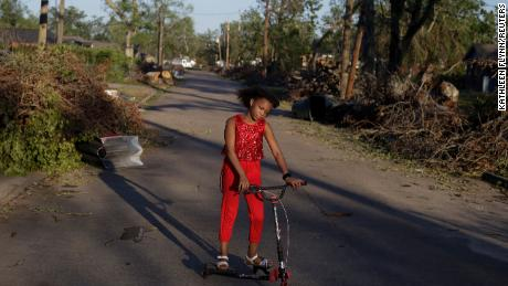 Iyana Sells, 9, plays on a debris-lined street Saturday after Hurricane Delta swept through Lake Charles.
