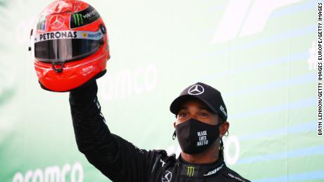 Lewis Hamilton ถือหมวกนิรภัยที่ Michael Schumacher สวมไว้ด้านบนหลังจากที่เขาผูกสถิติการชนะ F1 ของตำนานเยอรมันที่ Eifel GP