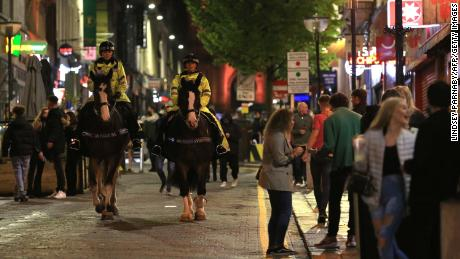 Police patrol as revelers enjoy a night out in the center of Liverpool, northwest England on Saturday, ahead of strict new measures planned in the area.