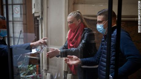 Customers receive hand sanitizer at the Chartier Bouillon Restaurant in Paris on Saturday.
