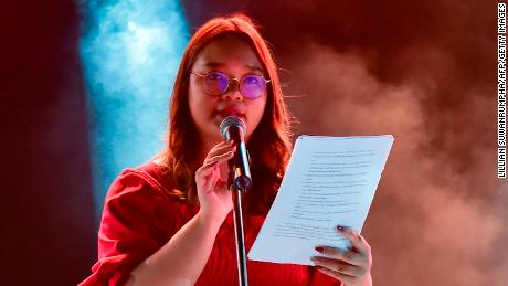Panusaya Sithijirawattanakul reads a list of demands during a pro-democracy rally at Thammasat University on August 10.