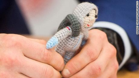 Expedition 64 crew member Sergey Kud-Sverchkov holds a knitted cosmonaut named Yuri made by his wife Olga.