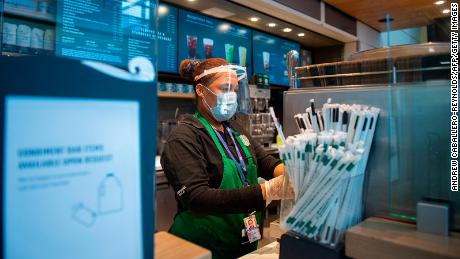 A Starbucks employee wears a face shield and mask as she makes a coffee in Ronald Reagan Washington National Airport in Arlington, Virginia.