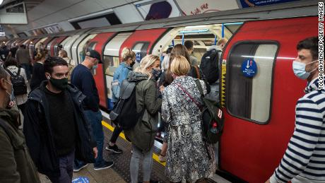 Commuters wearing masks crowd a London Underground train on September 23. The city will enter the