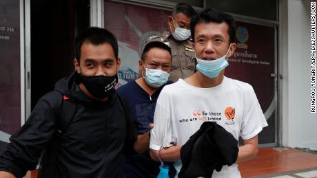 Thai pro-democracy activist Ekachai Hongkangwan (R) is escorted by police officers after being arrested, at Lat Phrao police station in Bangkok, on 16 October 2020.