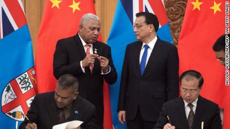 """Fiji's Prime Minister Josaia Voreqe """"Frank"""" Bainimarama talks with Chinese Premier Li Keqiang during a signing ceremony at the Great Hall of the People in Beijing on May 16, 2017."""