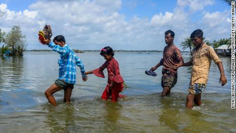 People cross the broken flooded road after the landfall of Cyclone Amphan in Bangladesh.
