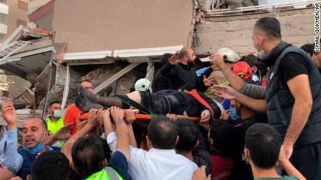 เจ้าหน้าที่กู้ภัยและคนในพื้นที่พาผู้บาดเจ็บที่พบในเศษซากอาคารที่ถล่มในอิซเมียร์เมื่อวันศุกร์