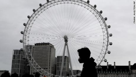 A man wearing a mask passes through the London Eye on Thursday as England prepares for a month-long lockdown.
