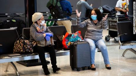 Passengers wear protective face masks while talking in Brazil's São Paulo/Guarulhos International Airport on March 15.