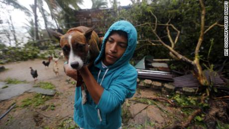 A man carries a dog to safety after Eta slams Nicaragua.