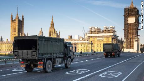 Military vehicles cross Westminster Bridge on March 24, 2020, after army personnel delivered a consignment of medical masks to St Thomas' Hospital, London.