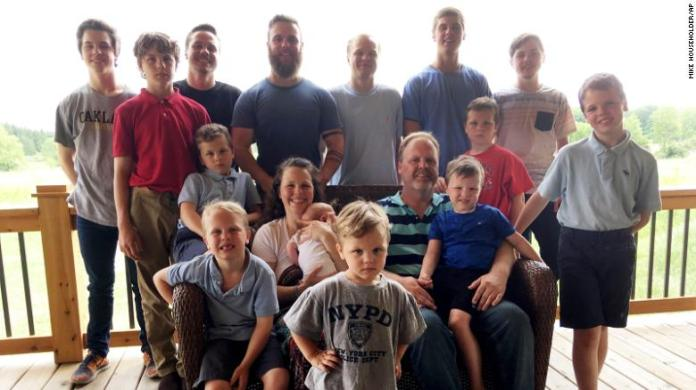 The Schwandt family poses for a photo in 2018 after welcoming their 14th son. Standing, from left, are Tommy, Calvin, Drew, Tyler, Zach, Brandon, Gabe, Vinny and Wesley. Seated, starting at upper left, are Charlie, Luke, mother Kateri holding Finley, father Jay with Tucker and Francisco in the foreground.