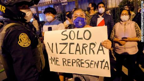 A woman displays a banner saying 'Only Vizcarra represents me' in Spanish on November 9, 2020.