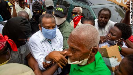 Yves Jean-Bart, wearing a light blue protective face mask, arrives at a courthouse for a hearing regarding allegations that he abused female athletes at the country's national training center in Croix-des-Bouquets, Haiti.