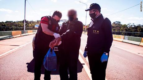 Brazilian police arrested fugitive Gonzalo Sanchez, center, in May as part of an operation by the Fugitive Investigative Support Unit of Interpol.  Interpol has smeared Sanchez's face according to his general policy.