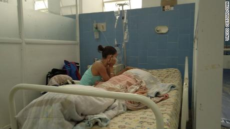 A woman pictured in Vargas Hospital in Caracas, Venezuela with her 69-year-old father, who she told CNN is suffering from malnourishment and sharing a ward with a Covid-19 patient despite his compromised immune system.