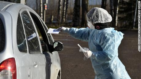 Medical workers take samples from patients on April 1, 2020 at a coronavirus drive-in testing center in Espoo, Finland.  (Jussi Nukari / Lehitikuwa / AFP)