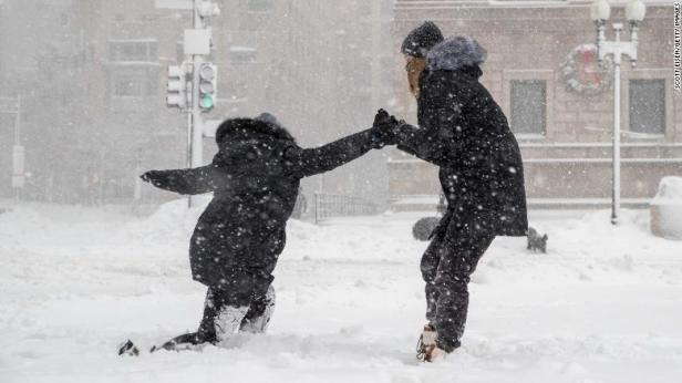 A woman helps her friend stand up after slipping on the sidewalk Thursday in Boston.