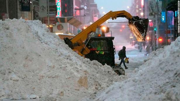A snowplow pushes snow near Times Square Thursday in New York.
