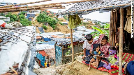 A family at Royhinga refugee camp Cox's Bazar in Bangladesh read with a Sesame Workshop character.