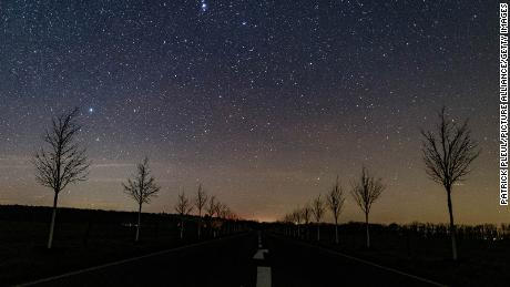 A small part of the Milky Way appears in the night sky above the streets in Brandenburg, Germany, on December 18, 2020.