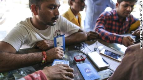 A customer holds a SIM card packet while waiting to connect his mobile phone to the carrier Reliance Jio, the mobile network of Reliance Industries, at a store in Mumbai, India, on Oct. 24, 2016.