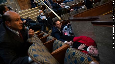 Rep. Jason Crow, a Colorado Democrat, comforts Rep. Susan Wild, a Pennsylvania Democrat, while taking cover as rioters seiged the US Capitol on January 6.
