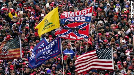 In this January 6, 2021 photo, supporters listen as President Donald Trump speaks during a rally in Washington that preceded the deadly assault on the US Capitol by his supporters.