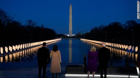"""With the Washington Monument in the background, President-elect Joe Biden with his wife Jill Biden and Vice President-elect Kamala Harris with her husband Doug Emhoff listen as Yolanda Adams sings """"Hallelujah"""" during a Covid-19 memorial on Jan. 19, 2021, in Washington. (AP Photo/Evan Vucci)"""