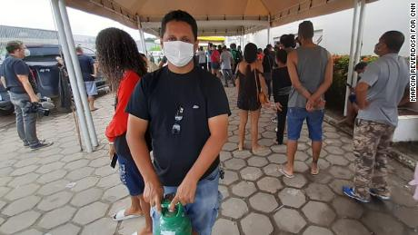 Joseney Costa Vicente queuing to buy oxygen for his mother Raquel, 69, in Manaus