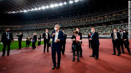 International Olympic Committee President Thomas Bach, wearing a face mask, speaks to the media during a visit to the Japan National Stadium on November 17, 2020 in Tokyo.