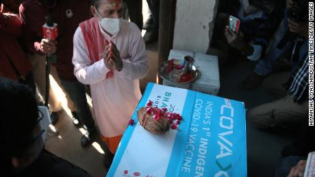 A priest performs prayer rituals on a carton containing the first consignment of Bharat Biotech's Covaxin vaccine.