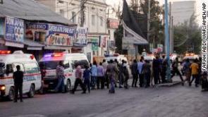 Ambulances and security forces gather on the street outside the Afrik hotel in Mogadishu on Sunday