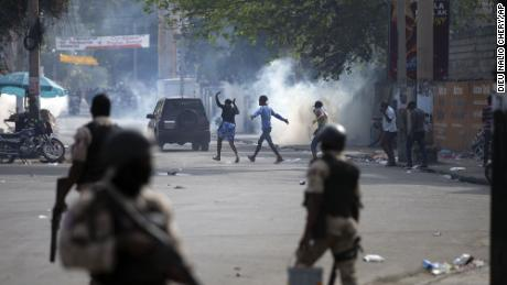 People walk across the street after the police fired tear gas during a nationwide strike demanding the resignation of Haitian President Jovenel Moise in Port-au-Prince, Haiti, on February 2.