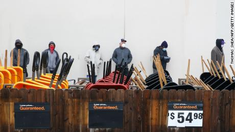Customers wait outside a Home Depot in Pearland, Texas to enter to buy the necessary supplies.