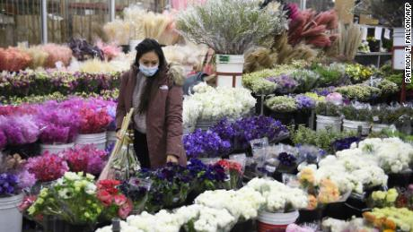 A customer wears a face mask while shopping for flowers in Los Angeles, California on February 12, 2021