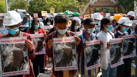 The graduates of Mandalay University bowed their heads as they held posters containing images of Maya Thowe Thwe Khine on February 14, 2021.