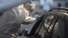 A medical worker takes a sample from a person at the drive-in coronavirus testing station in Prague.