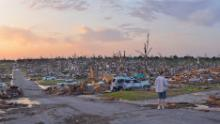 A person surveys damage one day after a tornado tore through Joplin, Missouri, killing dozens on May 23, 2011.