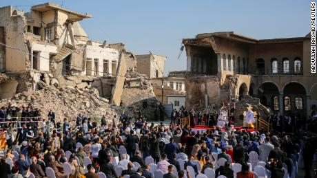 People attend a prayer led by Pope Francis for the victims of the war in the Church Square in the Old City of Mosul.