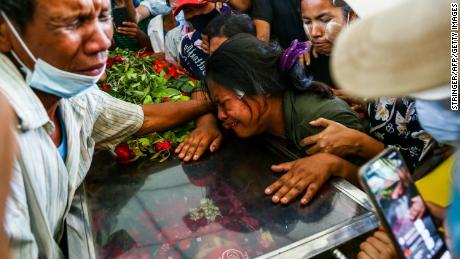 The wife of Phoe Chit, a protester who died during a demonstration against the military coup on March 3, cries over the coffin of her husband during his funeral in Yangon on March 5.