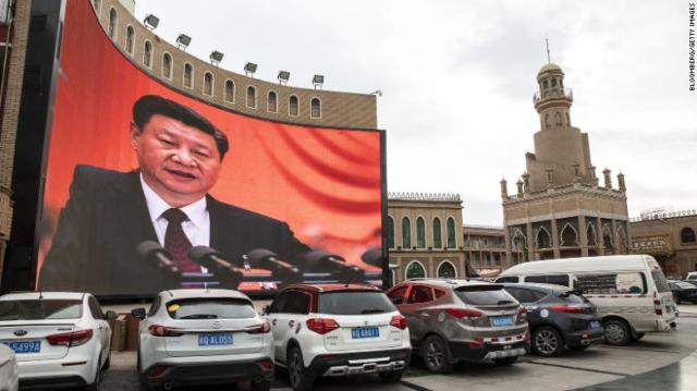 Vehicles stand in a parking lot as a large screen shows an image of Chinese President Xi Jinping in Kashgar, Xinjiang autonomousregion, China, on Thursday, November 8, 2018.
