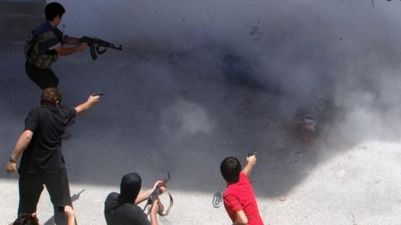 Rebel fighters execute two men on July 25, 2014, in Binnish, Syria. The men were reportedly charged by an Islamic religious court with detonating several car bombs.